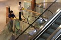 Cleaners disinfect handrails on escalators at Citygate Outlets shopping centre in Tung Chung. Photo: Nora Tam