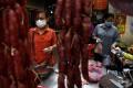 Women wearing masks buy pork at a market in Phnom Penh on September 15. The draft legislation includes a provision banning face masks. Photo: AFP