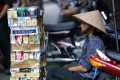 A cigarette vendor sits behind a pile of empty cartons of foreign and local cigarette brands on a Hanoi street on May 31. Vietnamese smokers can easily buy foreign brands at low prices thanks to persistent cigarette smuggling carried out through Vietnam's borders with Laos, Cambodia and China. Photo: AFP