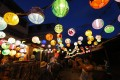 Visitors take photos of Mid-Autumn Festival lanterns hung along the streets at Tai O on September 27. Photo: Dickson Lee