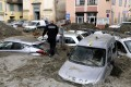 A police officer walks among vehicles submerged in mud in Breil-sur-Roya, south-eastern France, on Sunday. Photo: AFP