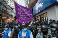 A police officer holds up a purple flag warning anti-government protesters they are violating the national security law. Photo: Felix Wong