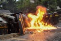 Riot police officers are hit by a petrol bomb in Bandung on Wednesday. Photo: AFP