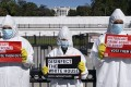 Wearing protective suits, masks and gloves, demonstrators call attention to the outbreak of coronavirus in the White House. Photo: AP