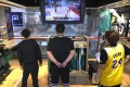 Employees at a Beijing NBA store watch the game between the LA Lakers and Miami Heat. Photo: AP
