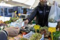 A customer hands a 20 Euro banknote to a vendor at a stall selling fruit and vegetables in Rome, Italy, earlier this month. Photo: Bloomberg