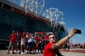 Manchester United fans pose for a photo outside the club's Old Trafford stadium. Photo: Reuters