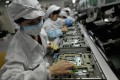 Workers assemble electronic components at a factory of Taiwanese technology giant Foxconn in Shenzhen, Guangdong province. Photo: AFP