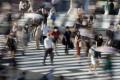 Pedestrians wearing face masks cross the road in Shibuya, Japan. Photo: EPA