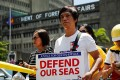 An activist holds a banner during a protest in Manila against the sinking of a Philippine fishing boat by a Chinese vessel in June 2019. Philippine military officials have raised the possibility of forming a seaborne militia. Photo: EPA