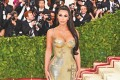 Kim Kardashian at the Met Gala in New York in 2018 wearing a gold Versace dress decorated with crosses. Photo: Courtesy of Versace