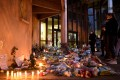 Flowers and candles are laid at the entrance of a school in Conflans-Sainte-Honorine, near Paris, after a teacher was decapitated. Photo: AFP