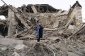 A woman stands near her destroyed house in Stepanakert, Nagorno-Karabakh. Photo: AP
