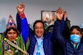Luis Arce (centre) of the Movement for Socialism celebrates with running mate David Choquehuanca (right) in La Paz, Bolivia on Monday. Photo: AFP