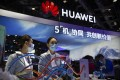 Staff members wearing face masks to protect against the coronavirus stand at a booth from Chinese technology firm Huawei at the PT Expo in Beijing, Wednesday, Oct. 14, 2020. Photo: AP