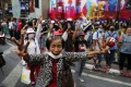 Pro-democracy protesters flashing three-fingered salutes near a main shopping district in Bangkok on Sunday. Photo: AP