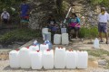 Malaysians wait to refill their containers from the natural springs in Shah Alam outside Kuala Lumpur after water supply was affected by the closure of treatment plants in Selangor river. Photo: EPA-EFE