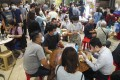 People eat lunch inside Haiphong Road Temporary Cooked Food Hawker Bazaar in Tsim Sha Tsui. Photo: Winson Wong