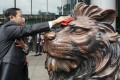"A staff member cleans one of HSBC's historic lion sculptures ahead of their unveiling outside the bank's headquarters in Central on October 22. The sculptures were restored after suffering damage during last year's protests. HSBC has come under increased scrutiny of late amid US sanctions and fears that China might place it on an ""unreliable entities"" list. Photo: Felix Wong"