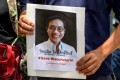 A protester holds a portrait of allegedly kidnapped Thai activist Wanchalerm Satsaksit. Photo: AFP