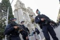 Police officers stand guard by the Notre-Dame basilica in Nice. Photo: AFP
