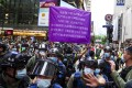 A police officer raises a purple banner warning protesters in Causeway Bay on October 1 that they might be violating the national security law, which took effect just before midnight on July 1. Photo: Sam Tsang