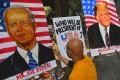 An artist paints an image of Joe Biden next to a painting of US President Donald Trump in Mumbai, India. Photo: AFP