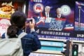 A passer-by takes a photo of a news report on the US election playing on a screen in Tsim Sha Tsui on Wednesday. Photo: Dickson Lee