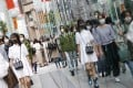 People wearing face masks walk in Tokyo's Ginza area. An huge drop in foreign nationals arriving in Japan this year has left the luxury retail market reeling. Photo: Kyodo News via Getty Images