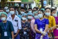 People wearing face shields, face masks and rubber gloves to prevent the spread of the coronavirus wait to vote during the elections at a polling station in Yangon on Sunday. Photo: AFP