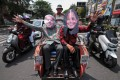 Local residents wearing masks of Joe Biden and Kamala Harris wave as they ride on a trishaw along a street in Solo, central Java, Indonesia. Photo: AFP