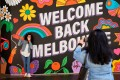 FILE PHOTO: People take photos in front of a 'Welcome Back' sign in Melbourne after coronavirus disease (COVID-19) restrictions were eased for the state of Victoria, Australia, October 28, 2020. REUTERS/Sandra Sanders/File Photo
