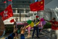 Pro-Beijing demonstrators wave the flags of China (right) and the Hong Kong Special Administrative Region, as they celebrate outside the Legislative Council in Hong Kong on November 12. China's top legislative body on November 11 passed a resolution allowing for the disqualification of any Hong Kong lawmakers not deemed sufficiently loyal. Photo: Bloomberg