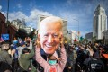 A woman holds a Joe Biden mask as people march in celebration in Los Angeles after he was declared the winner of the presidential election, on November 7. Photo: AFP