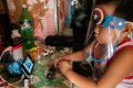 A boy wears a face shield while watching an online learning programme on a smartphone in Manila, Philippines, on August 17. Photo: Reuters