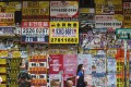 Pedestrians pass a store covered in posters for property agents in Causeway Bay, Hong Kong. Photo: K. Y. Cheng