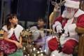 Gracelynn Blumenfeld, 8, visits with Santa through a transparent barrier in Bridgeport, Connecticut. Photo: AP