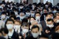 Office workers wearing face masks are seen at Shinagawa station in Tokyo, as the Japanese capital battles an outbreak in Covid-19 cases. Photo: Reuters