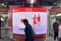 Commuters walk past an advertisement for online commerce site Shopee at a Bangkok skytrain station. Photo: SCMP / Chua Kong Ho