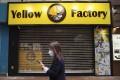 A woman walks past a Yellow Factory store in Mong Kok. Photo: Sam Tsang