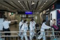An official gestures travellers in protective gear towards a quarantine area in the arrivals hall of Hong Kong International Airport on July 15. Photo: Bloomberg