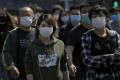 People wearing protective face masks to prevent the spread of the new coronavirus walk across a street in Beijing on Sunday, April 12, 2020. Photo: Andy Wong