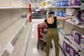 A shopper picks up a roll of toilet paper at a store in Burbank, California. Photo: AFP