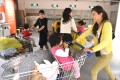 A group of Chinese mothers go shopping with their children at a furniture store in Beijing. A survey has highlighted the problems working mothers face in China. Photo: AFP