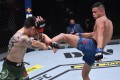 Brandon Royval kicks Brandon Moreno in their flyweight bout during UFC 255. Photos: Jeff Bottari/Zuffa LLC via Getty Images
