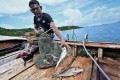 Fisherman Sanam Changnam shows his daily catch of fish off the coast of the southern Thai island of Phuket. Photo: AFP