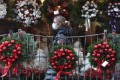 A woman walks past Christmas wreaths displayed for sale in Denny, Scotland. Photo: PA Wire/dpa