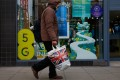 A pedestrian passes an EE store advertising 5G network capabilities in London, U.K., on Tuesday, Nov. 24, 2020. The U.K. is considering a ban on the installation of Huawei Technologies Co. 5G equipment as soon as next year to appease hawks pushing for tighter restrictions on the Chinese network equipment maker, according to people familiar with the matter. Photographer: Hollie Adams/Bloomberg