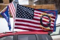 A car with a QAnon flag drives by as supporters of President Donald Trump gather for a rally in Minnesota earlier this month. Photo: AFP