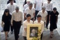 Lee Suet Fern (far left) and other family members of the late Lee Kuan Yew arrive with his portrait at the start of the state funeral at the University Cultural Centre in Singapore on March 29, 2015. Photo: AP